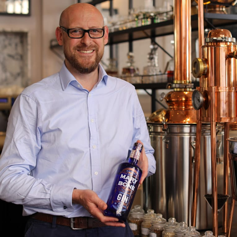 Johnny Neill holding a bottle of Marylebone gin